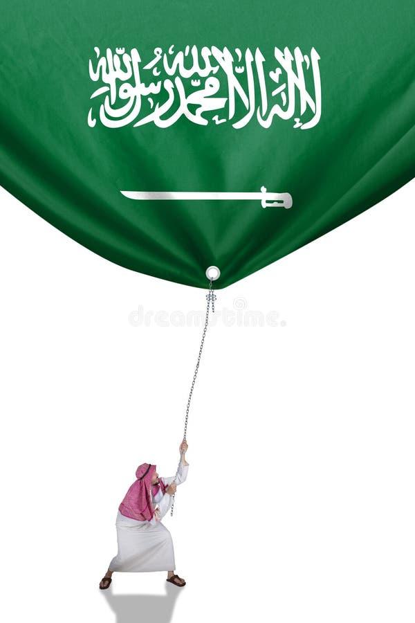 A pessoa do Oriente Médio puxa a bandeira árabe fotos de stock