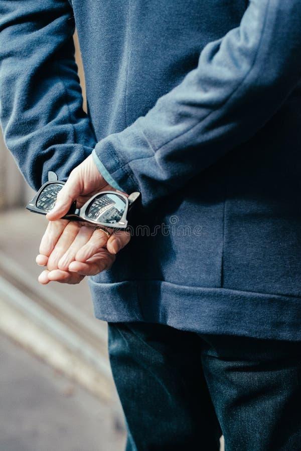 Pessoa em um casaco azul com m?os atr?s dos ?culos de sol da terra arrendada da parte traseira imagem de stock royalty free