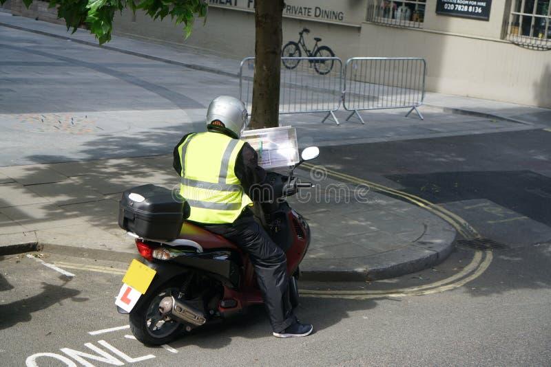 A pessoa em uma tentativa do 'trotinette' para recordar estradas em Londres para o taxista de Londres testa fotografia de stock royalty free