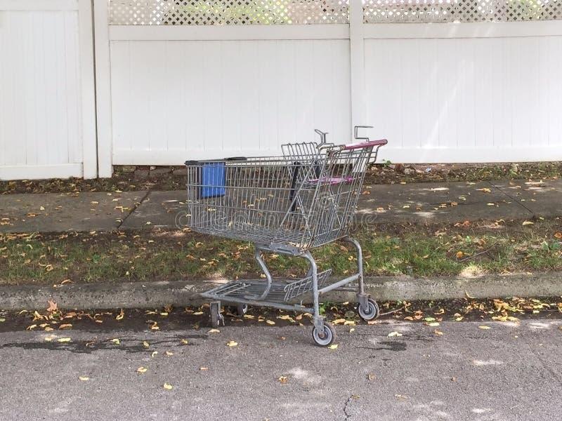 A pessoa esquecido idosa deixa o carrinho de compras na rua fotografia de stock