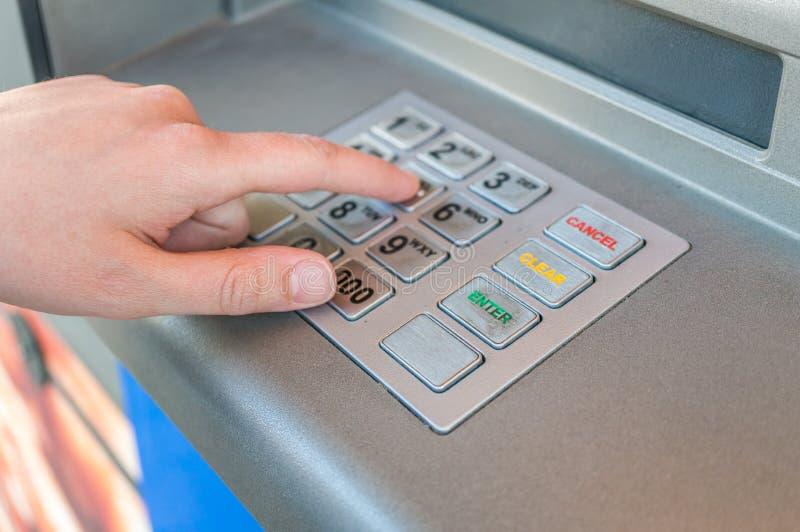 A pessoa está usando o teclado e o código entrando do pino na máquina do ATM Conceito da operação bancária fotos de stock