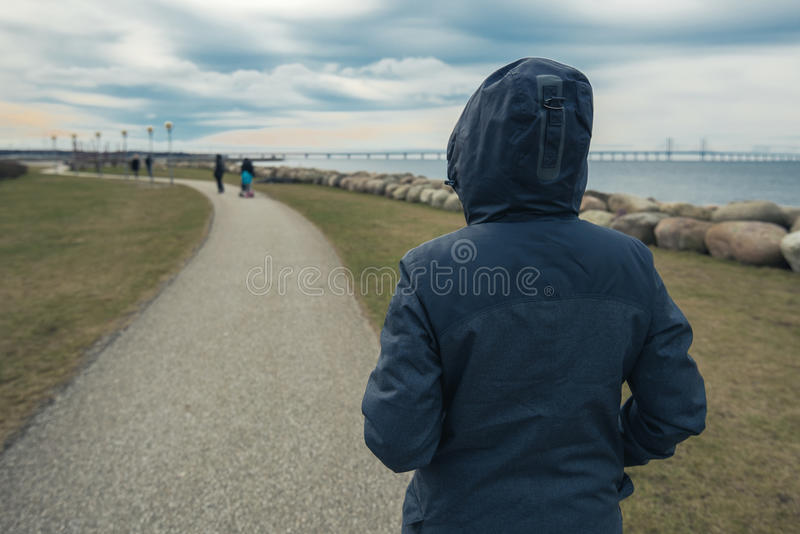 Pessoa fêmea encapuçado só da posição de trás no litoral foto de stock royalty free
