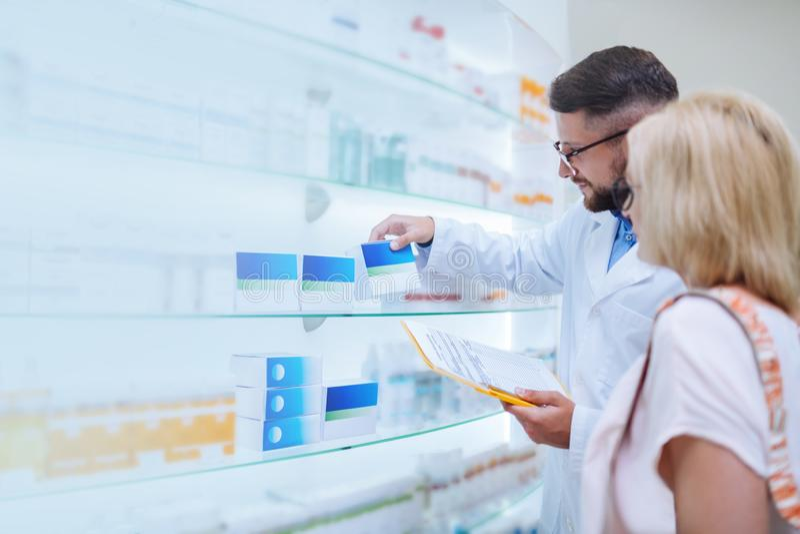 Pessoa fêmea madura concentrada que escuta o farmacêutico imagens de stock