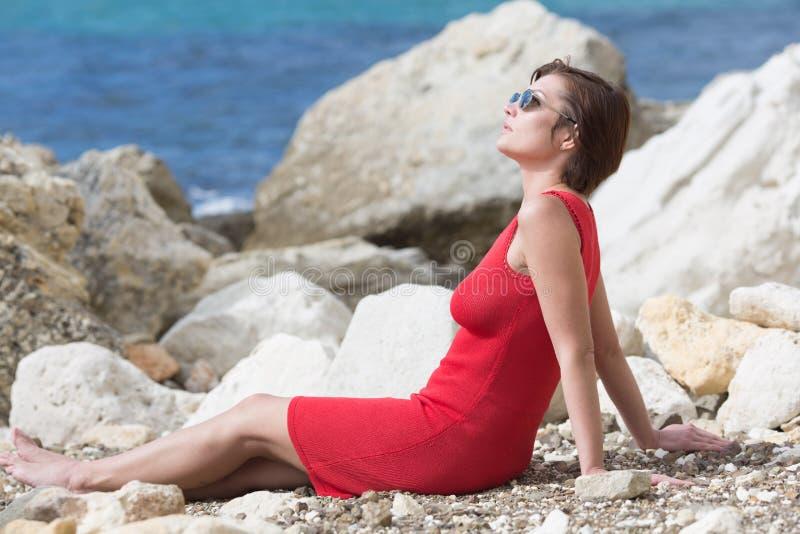 Pessoa fêmea que descansa no litoral rochoso imagem de stock royalty free