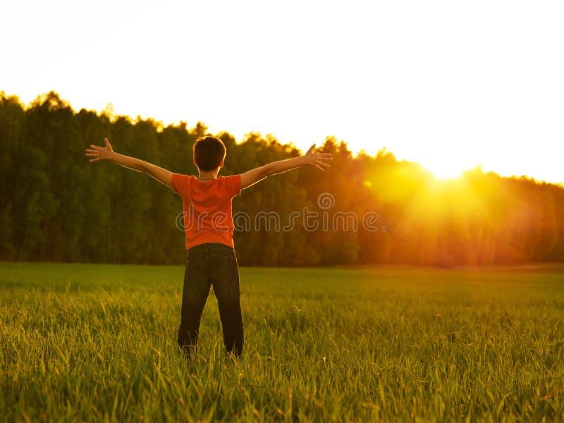 Pessoa feliz no campo com os braços aumentados no por do sol imagem de stock
