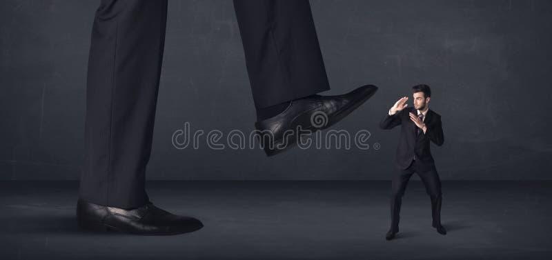Pessoa gigante que pisa em um conceito do homem de negócios pequeno imagem de stock royalty free