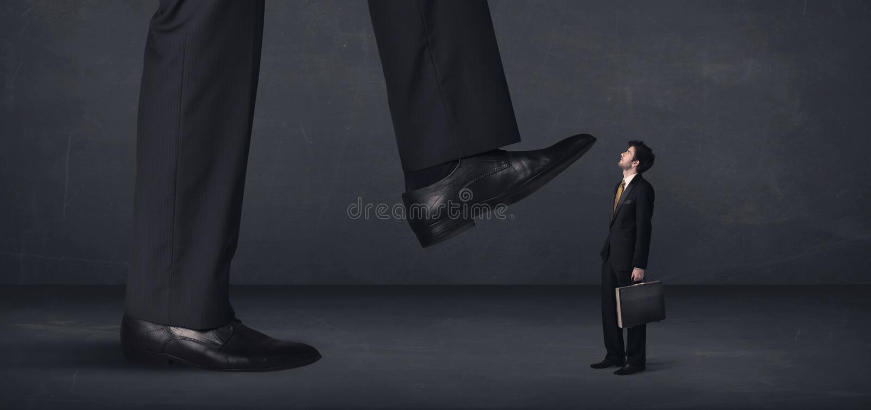Pessoa gigante que pisa em um conceito do homem de negócios pequeno fotografia de stock