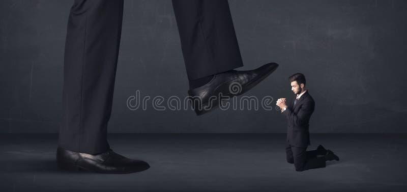 Pessoa gigante que pisa em um conceito do homem de negócios pequeno imagens de stock royalty free