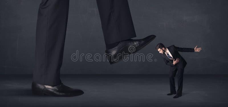 Pessoa gigante que pisa em um conceito do homem de negócios pequeno foto de stock royalty free