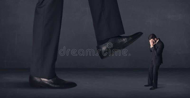 Pessoa gigante que pisa em um conceito do homem de negócios pequeno imagem de stock