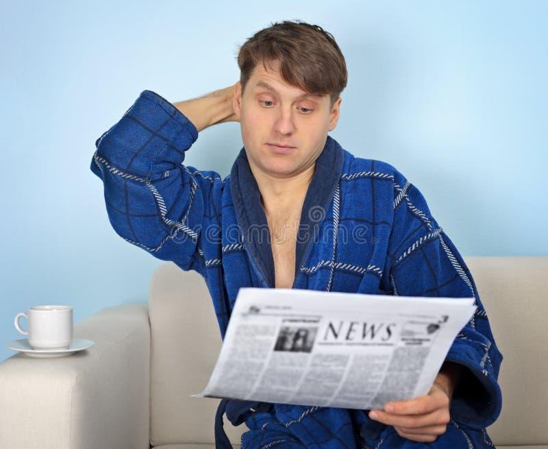 A pessoa lê um jornal com pensiveness imagens de stock royalty free