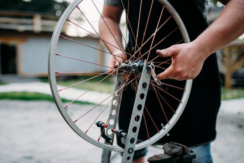 A pessoa masculina ajusta raios e roda da bicicleta fotografia de stock royalty free
