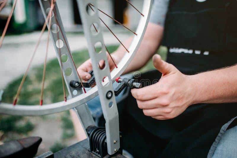 A pessoa masculina ajusta raios e roda da bicicleta imagens de stock royalty free