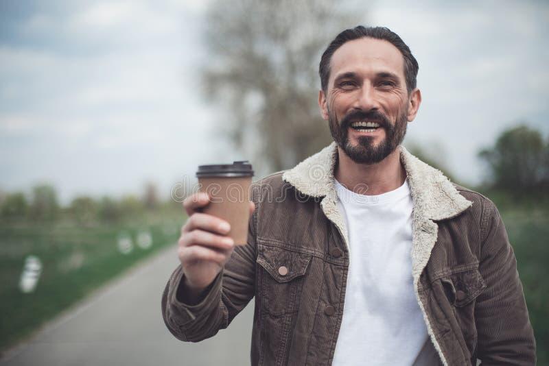 Pessoa masculina feliz que mantém o copo da bebida quente exterior fotos de stock