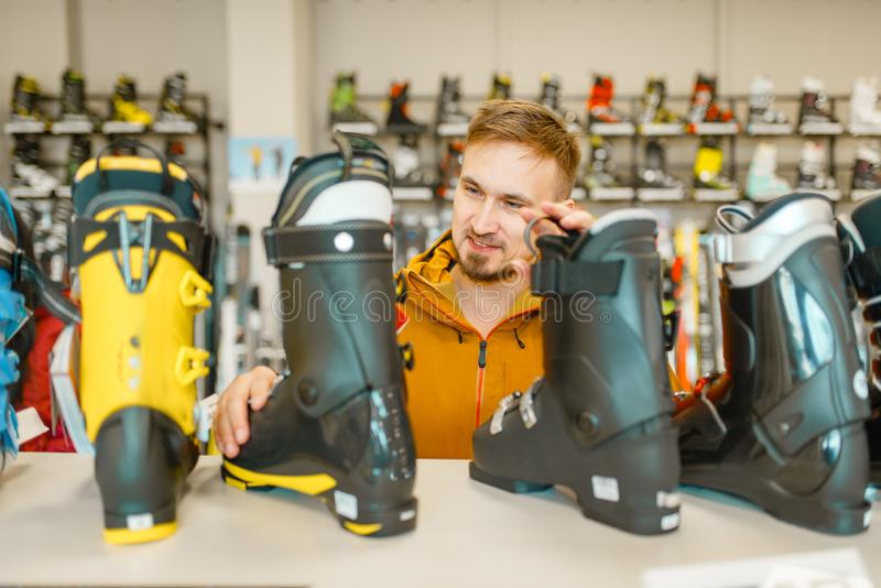 Pessoa masculina que escolhe botas do esqui ou da snowboarding fotografia de stock royalty free