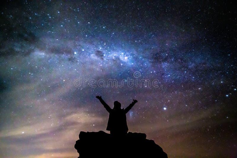 A pessoa mostrada em silhueta sauda o céu noturno estrelado da Via Látea do cosmos fotos de stock royalty free