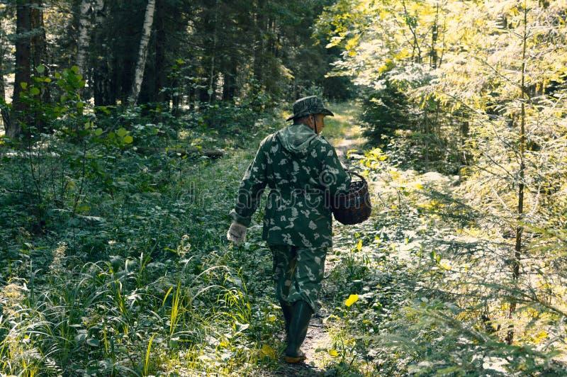Pessoa na roupa da camuflagem com uma cesta fotografia de stock