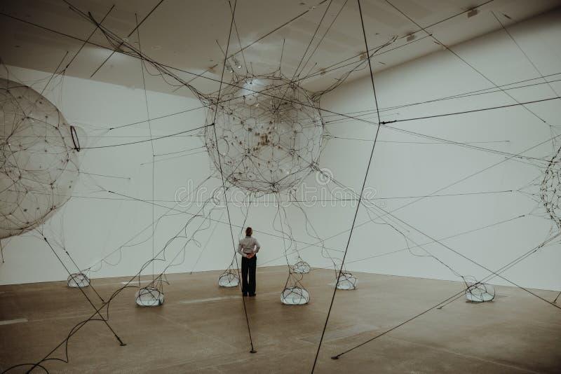 Pessoa na sala do museu com a instalação da arte foto de stock royalty free