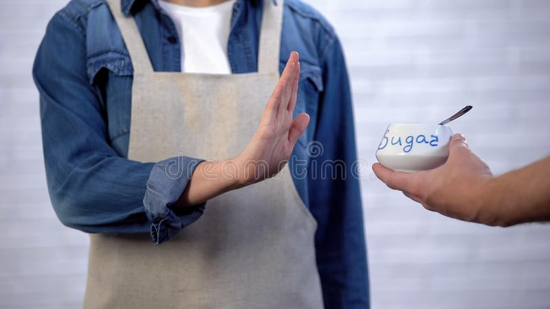 Pessoa no avental que não gesticula nenhum açúcar no cozimento, no risco de diabetes e na obesidade fotografia de stock
