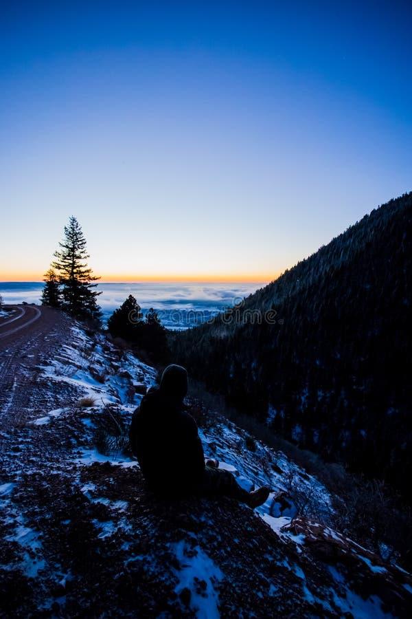 A pessoa olha o por do sol da estrada nevado da montanha imagem de stock royalty free