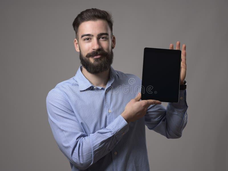 Pessoa ou programador farpado novo de sorriso feliz do negócio que mostram a tela da tabuleta com espaço vazio para anunciar fotografia de stock royalty free