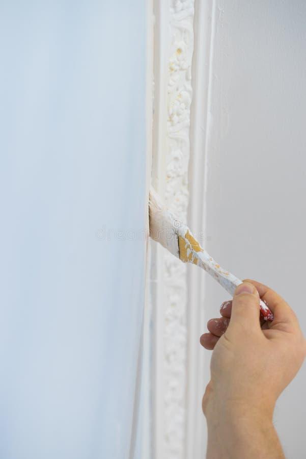 Pessoa que aplica a pintura na parede foto de stock royalty free