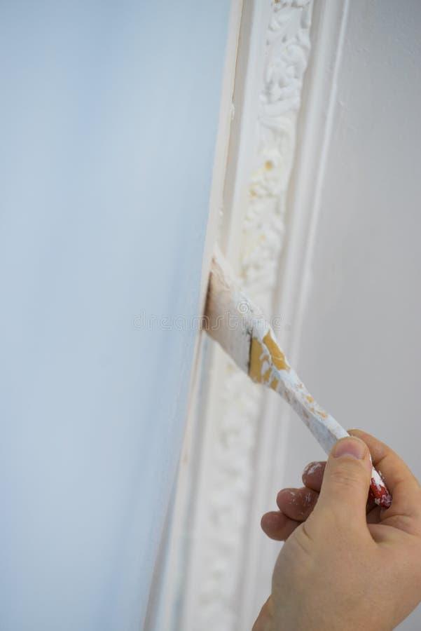 Pessoa que aplica a pintura na parede imagens de stock