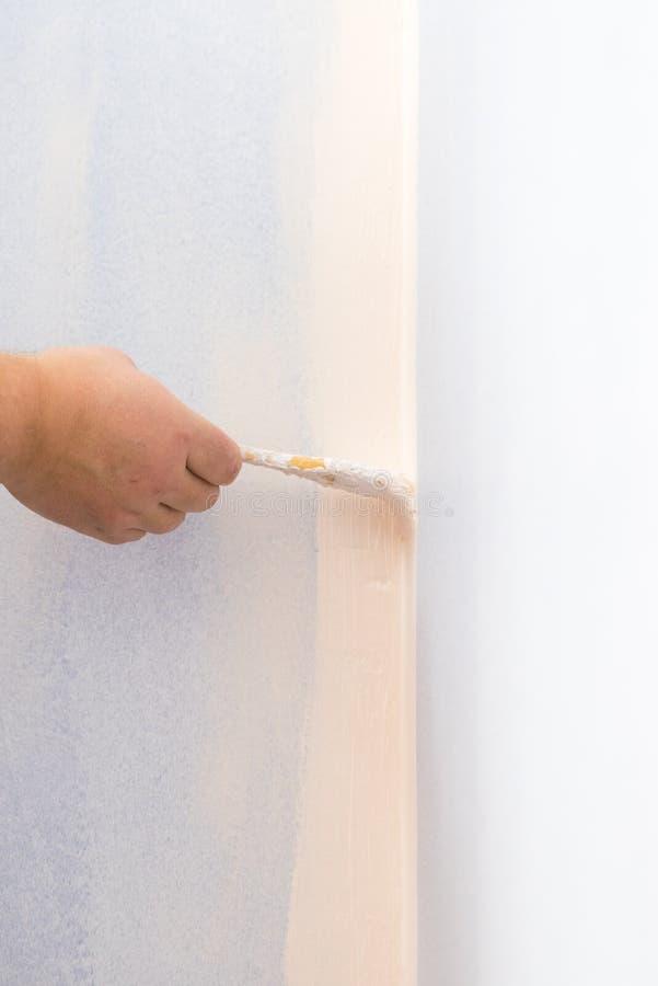 Pessoa que aplica a pintura na parede imagem de stock