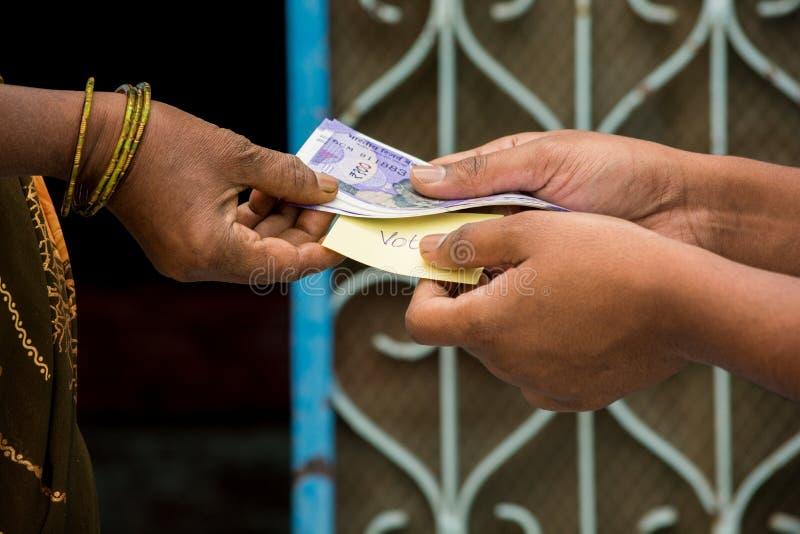 Pessoa que dá o dinheiro à mulher para o voto na frente da porta, conceito de mostrar um dinheiro para o voto fotos de stock