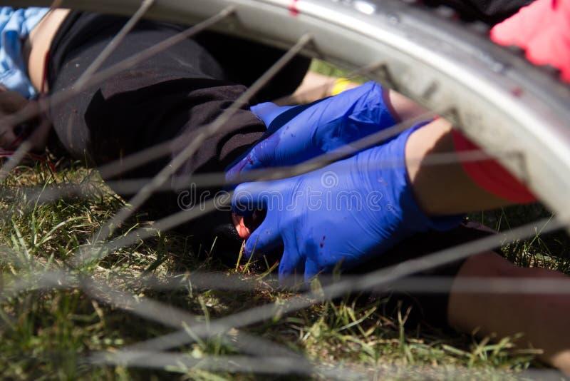 Pessoa que dá uns primeiros socorros após o impacto da bicicleta imagem de stock