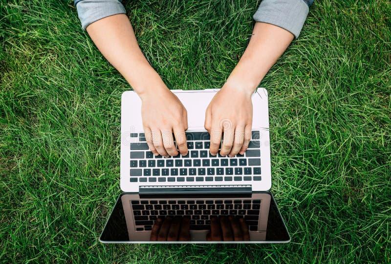 Pessoa que datilografa no portátil com tela vazia fora fotografia de stock