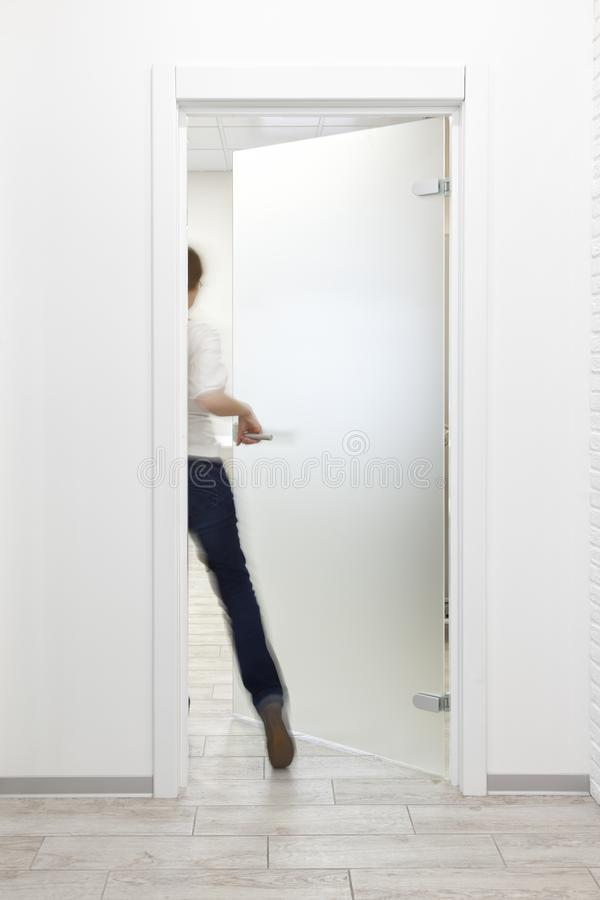 Pessoa que entra em uma sala no escritório com interior branco minimalista imagem de stock