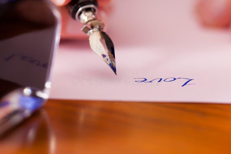 Pessoa que escreve uma letra de amor com pena e tinta imagens de stock royalty free