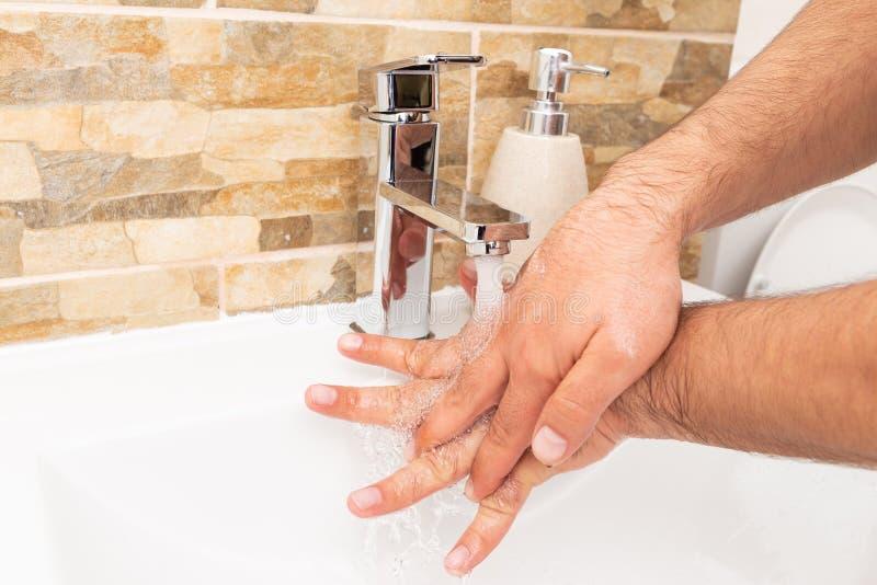 Pessoa que guarda as mãos sob a água imagem de stock