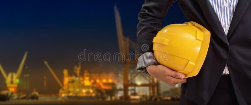 Pessoa que guarda o capacete amarelo para a segurança dos trabalhadores no fundo industrial do porto na noite imagens de stock
