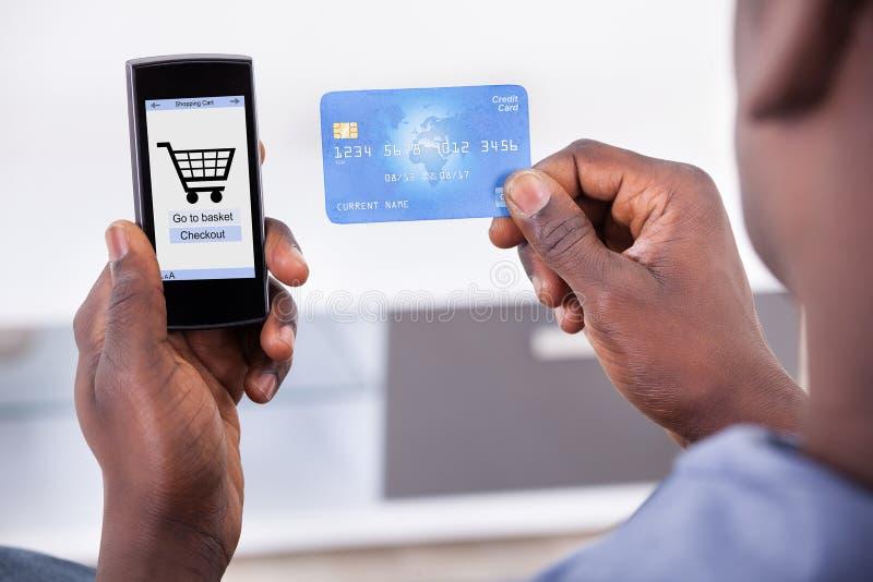 Pessoa que guarda o cartão e o telefone celular de crédito fotos de stock