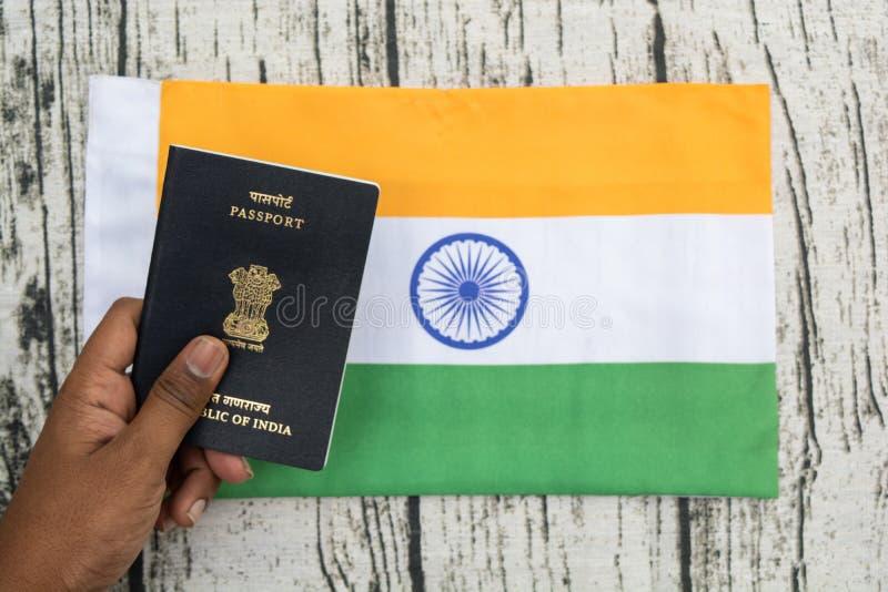 Pessoa que guarda o passaporte indiano com mão em uma bandeira indiana como o fundo fotos de stock royalty free