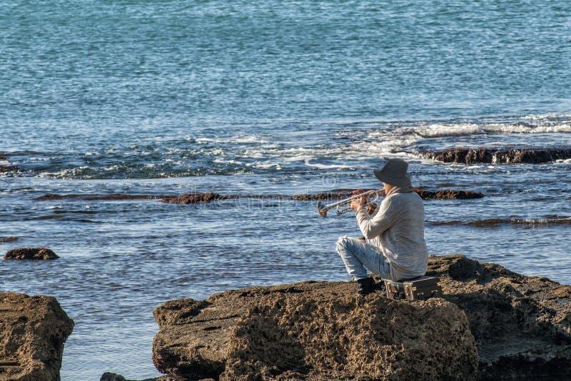 Pessoa que joga o saxofone que senta-se nas rochas na frente de um mar bonito imagem de stock