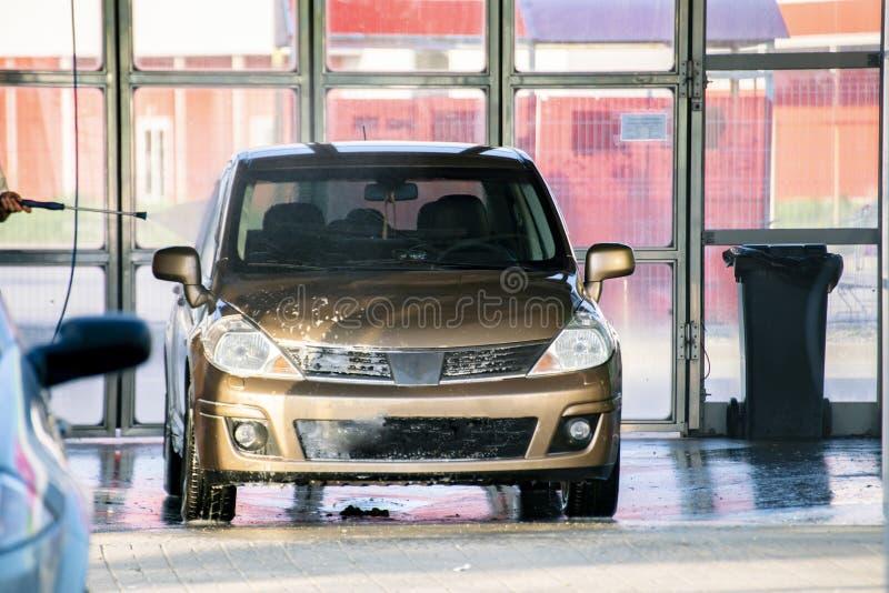 Pessoa que lava seu carro em um woth da estação um líquido de limpeza especial, serviços da lavagem de carros imagens de stock royalty free