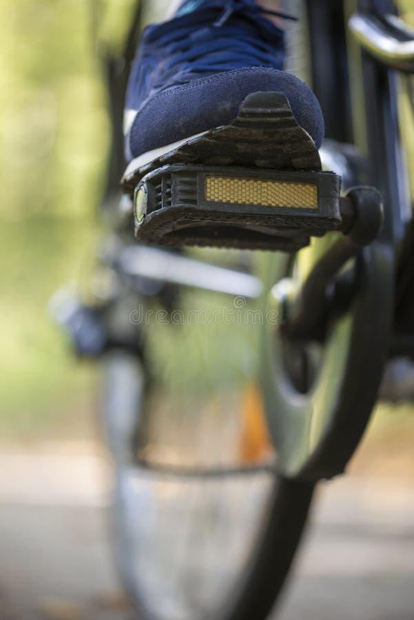 Pessoa que monta uma bicicleta em uma ideia de baixo ângulo do pé fotos de stock royalty free