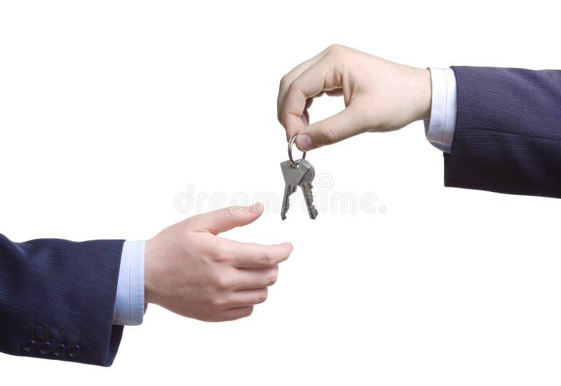 Pessoa que passa chaves da porta imagens de stock