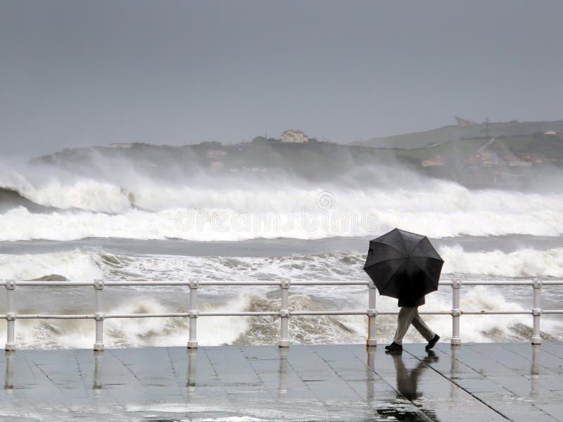 Pessoa que protege com guarda-chuva em um dia chuvoso e ventoso imagem de stock royalty free