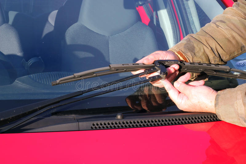 Pessoa que repara o limpador de pára-brisa. imagens de stock