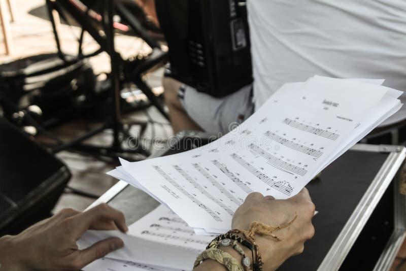 Pessoa que segura folhas de notas musicais brancas fotos de stock royalty free