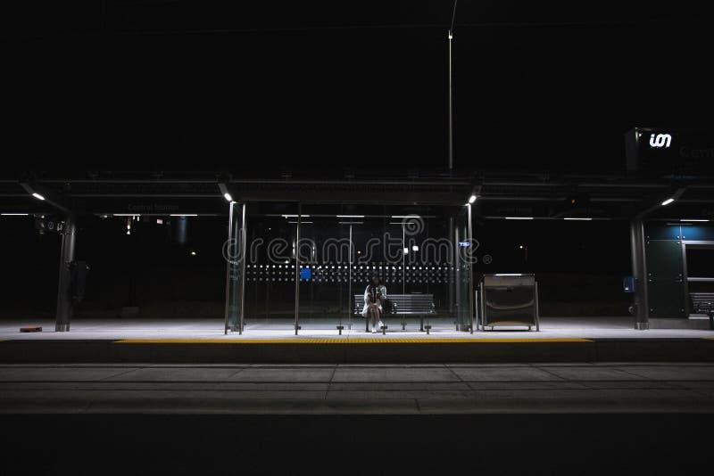 Pessoa que senta na parada do ônibus todo o apenas atrasado na noite foto de stock