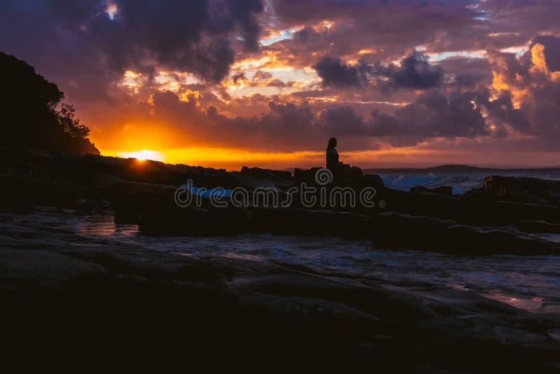 Pessoa que senta-se na rocha no mar do por do sol fotos de stock