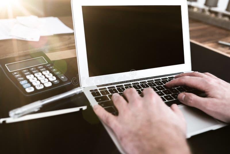 Pessoa que senta-se no funcionamento da mesa na datilografia no laptop imagem de stock royalty free