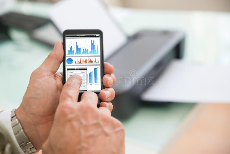 Pessoa que usa o telefone celular para imprimir imagem de stock