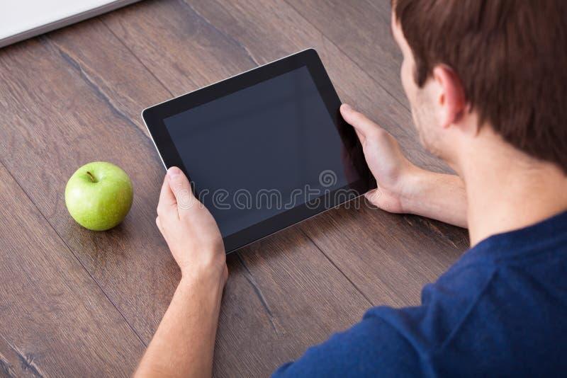 Pessoa que usa a tabuleta digital além da maçã verde fotografia de stock royalty free