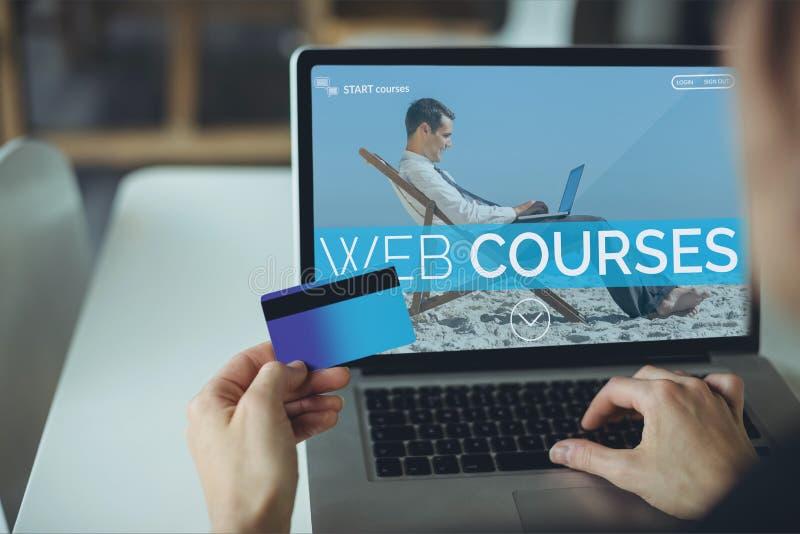 Pessoa que usa um computador com informação do ensino eletrónico na tela foto de stock royalty free